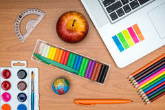 Fournitures scolaires et comprimé sur le bureau en bois d'école d'en haut Photos libres de droits