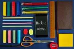 Fournitures scolaires et papeterie sur le fond bleu Images stock