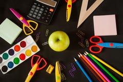 Fournitures scolaires et pomme devant un tableau noir Images stock
