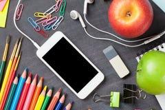 Fournitures scolaires et smartphone sur le fond de tableau noir Images libres de droits