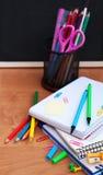 Fournitures scolaires et tableau noir Photo stock