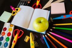 Fournitures scolaires et une grande pomme verte sur le bloc-notes au centre Image stock