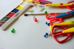Fournitures scolaires - peinture, trombones, brosse, ciseaux Photo stock