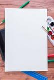 Fournitures scolaires sous une feuille de livre blanc avec l'espace de copie Photographie stock libre de droits