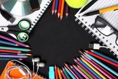 Fournitures scolaires sur le cadre de tableau noir image stock