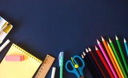 Fournitures scolaires sur le fond bleu-foncé De nouveau au concept d'?cole photographie stock libre de droits