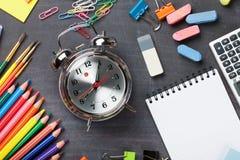 Fournitures scolaires sur le fond de tableau noir Photo stock