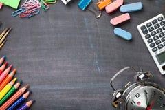 Fournitures scolaires sur le fond de tableau noir Images stock