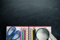 Fournitures scolaires sur le fond de tableau noir Photographie stock libre de droits