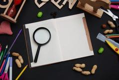 Fournitures scolaires sur le fond de tableau noir avec le carnet ouvert pour des notes De nouveau au concept d'école Vue supérieu photos libres de droits