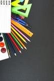 Fournitures scolaires sur le fond de tableau noir avec le copyspace pour votre texte, conception De nouveau au concept d'école po Photographie stock