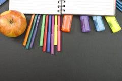 Fournitures scolaires sur le fond de tableau noir avec le copyspace pour votre texte, conception De nouveau au concept d'école po Photos libres de droits