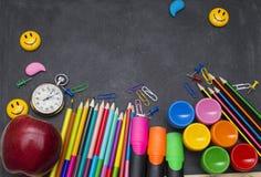 Fournitures scolaires sur le fond de tableau noir prêt pour votre conception Photographie stock libre de droits