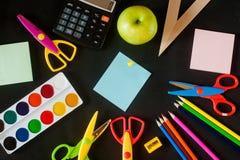 Fournitures scolaires sur le fond de tableau noir prêt pour votre conception Images stock