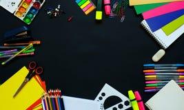 Fournitures scolaires sur le fond de tableau noir prêt pour votre conception photos stock