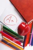 Fournitures scolaires sur un fond blanc avec une pomme et avec un n Photo stock