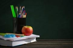 Fournitures scolaires sur une surface en bois contre un tableau noir Photographie stock libre de droits