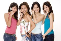 Foursome #1. Four beautiful young asian women using their phones Royalty Free Stock Images