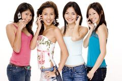 Foursome #2. A group of four young asian women all using their phones Stock Photo