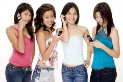 Foursome #3. Four attractive young women using their phones (cellphones/mobiles Stock Photo