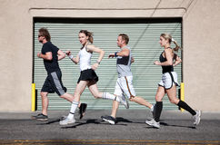 Foursome runs in the city for exercise. Beautiful, confident woman runs with friends Stock Photography