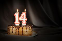 Fourteen years anniversary. Birthday chocolate cake with white burning candles in the form of number Fourteen. Dark background with black cloth stock images