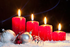 Fourth advent. Four red candles with christmas balls in snow for fourth advent royalty free stock photos