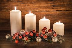 Fourth Advent. Christmas decoration with christmas bauble, red berries, fir branches and candles for Advent season four candles burning Royalty Free Stock Photo