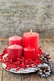 Four candles in a white wreath with red berries on a wooden rustic background. advent calendar for Christmas stock images