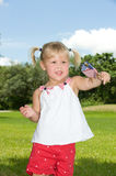Fourth of July. Adorable little blond girl in red white and blue waving an American flag Royalty Free Stock Image