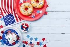 Fourth of July american Independence Day background decorated with USA flag, donut with candys, stars and confetti. Stock Photo
