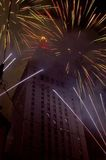 Fourth Of July Celebration. Fireworks surround a building during a Fourth of July celebration.  Multicolor bursts go off behind the building while Bluish white Royalty Free Stock Photography