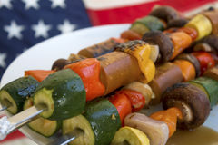 Fourth of July feast. Barbecue on skewers with mushrooms, zucchini, tomatoes, peppers, garlic, and vegan sausage at a 4th of July celebration party Royalty Free Stock Image