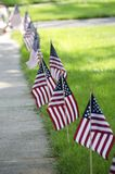 Fourth of July. Flags along the edge of the lawn and sidewalk decorating for the Fourth of July holiday in a small American town Royalty Free Stock Photo