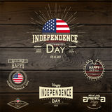Fourth of July Independence Day USA badges logos and labels for any use. On wooden background texture Stock Images