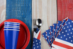 Fourth of July Picnic Table Setting. High angle photo of a Fourth of July picnic table setting. The red white and blue items are on a wood table painted for the Stock Photos