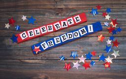 Fourth of July Sign with Words that say Celebrate Freedom.  It`s in red, white and blue with shiny stars with light reflections,. All on rustic dark wood board royalty free stock photography