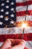 Fourth of July Sparkler. A fourth of july sparkler on a usa flag background royalty free stock photo
