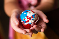 Fourth of July Star Cupcakes. A child holding a Fourth of July cupcake decorated with red, white and blue star sprinkles Royalty Free Stock Photography