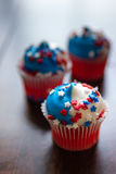 Fourth of July Star Cupcakes. Three Fourth of July cupcakes decorated with red, white and blue star sprinkles Royalty Free Stock Images