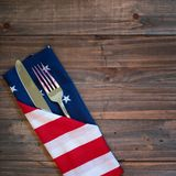 Fourth of July Table Place Setting with a fork, knife and flag napkin on rustic wood board background with room or space for copy,