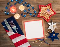Fourth of July Table Place Setting with red, white and blue decorations and blank card with copy space. It`s a horizontal crop wit
