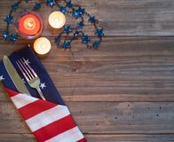 Fourth of July Table Place Setting with Rustic Wood Board Background with copy space, lighted candles and blue star beads.  It`s