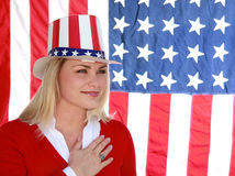 Fourth of July Woman. Pretty young blonde woman wearing a stars and stripes hat, in front of the american flag Royalty Free Stock Image