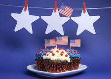 USA American flags with stars hanging from pegs on a line and cupcakes with copy space. Stock Photography