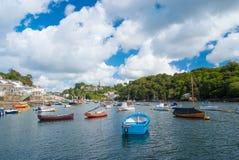 Fowey, Royaume-Uni - 24 mars 2010 : bateaux dans le port de mer sur le ciel nuageux Vitesse et bateaux à voile sur l'eau Été Photos libres de droits