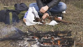 Fowl preparing, Hunting theme. Hands of man pull out a feathers of colorful Pheasant Fowl Near the bonfire. Plucking a