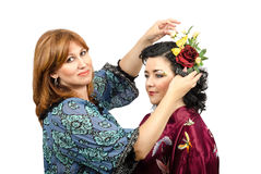 Fox-coloured hairstylist putting roses and butterfly in her hair Royalty Free Stock Images