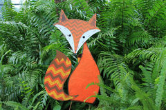 Fox in ferns. Red fox holiday decoration surrounded by green ferns in the background royalty free stock photography