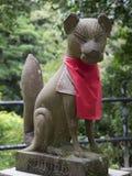 Fox figure in kiyomizu-dera Temple. Kiyomizu Temple, Kyoto, Japan - June 28, 2014 : A Fox figure gurdien of Shine sit on stone with tree background Royalty Free Stock Image